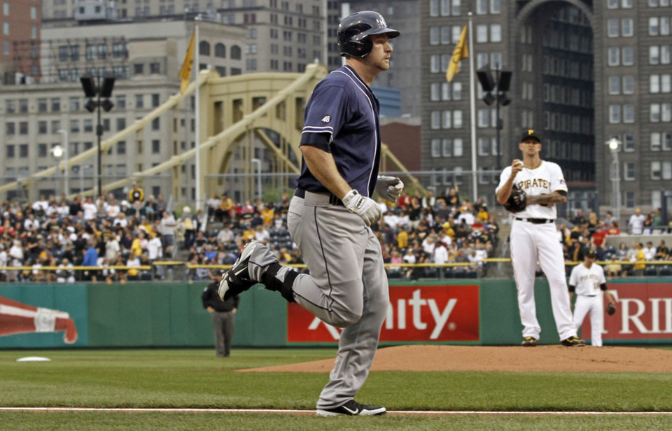 Photo -   San Diego Padres' Chase Headley, left, runs past Pittsburgh Pirates starting pitcher A.J. Burnett after hitting a home run off him in the first inning of the baseball game on Saturday, Aug. 11, 2012, in Pittsburgh. (AP Photo/Keith Srakocic)