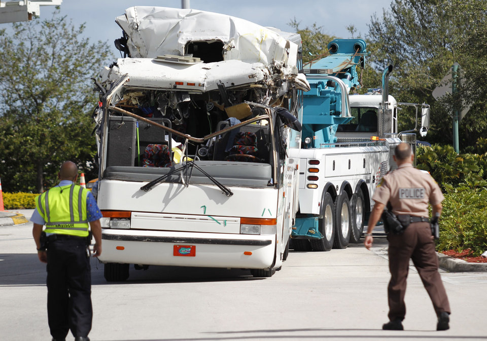 Photo - Law enforcement officers watch as a bus which hit a concrete overpass at Miami International Airport is hauled away, Saturday, Dec. 1, 2012 in Miami. The vehicle was too tall for the 8-foot-6-inch entrance to the arrivals area, and buses are supposed to go through the departures area which has a higher ceiling, according to an airport spokesperson. (AP Photo/Wilfredo Lee) (AP Photo/Wilfredo Lee)