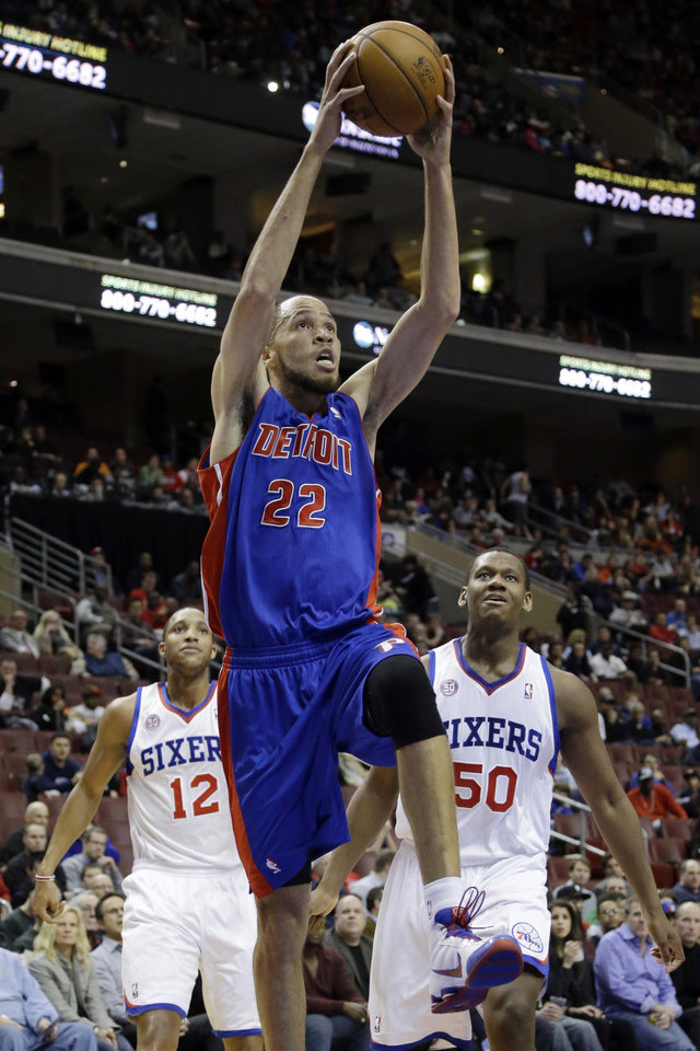 Photo - Detroit Pistons' Tayshaun Prince, center, goes up for a dunk past Philadelphia 76ers' Evan Turner, left, and Lavoy Allen in the first half of an NBA basketball game, Monday, Dec. 10, 2012, in Philadelphia. (AP Photo/Matt Slocum)