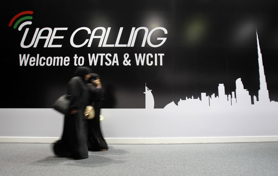 Photo - Emirati women pass by a billboard on the final day of World Conference on International Telecommunications in Dubai, United Arab Emirates, Friday, Dec. 14, 2012. Envoys in Dubai signed a new U.N. telecommunications treaty Friday that a U.S.-led delegation says endorses greater government control of the Internet. The U.S. and more than 20 other countries refused to ratify the accord by the 193-nation International Telecommunications Union.(AP Photo/Kamran Jebreili)
