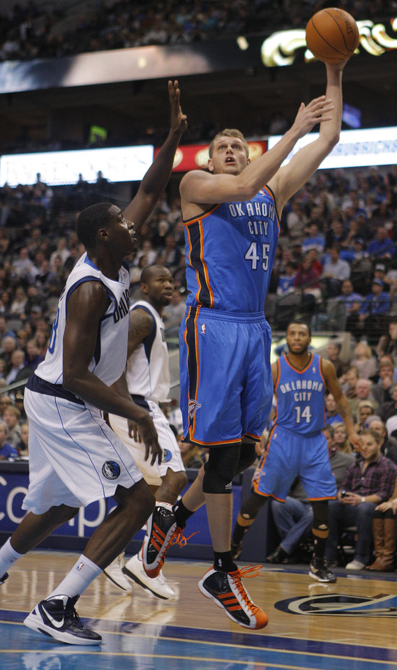 Photo - Oklahoma City's Cole Aldrich (45) shoots as Dallas' Ian Mahinmi (28) defends during the pre season NBA game between the Dallas Mavericks and the Oklahoma City Thunder at the American Airlines Center in Dallas, Sunday, Dec. 18, 2011. Photo by Sarah Phipps, The Oklahoman