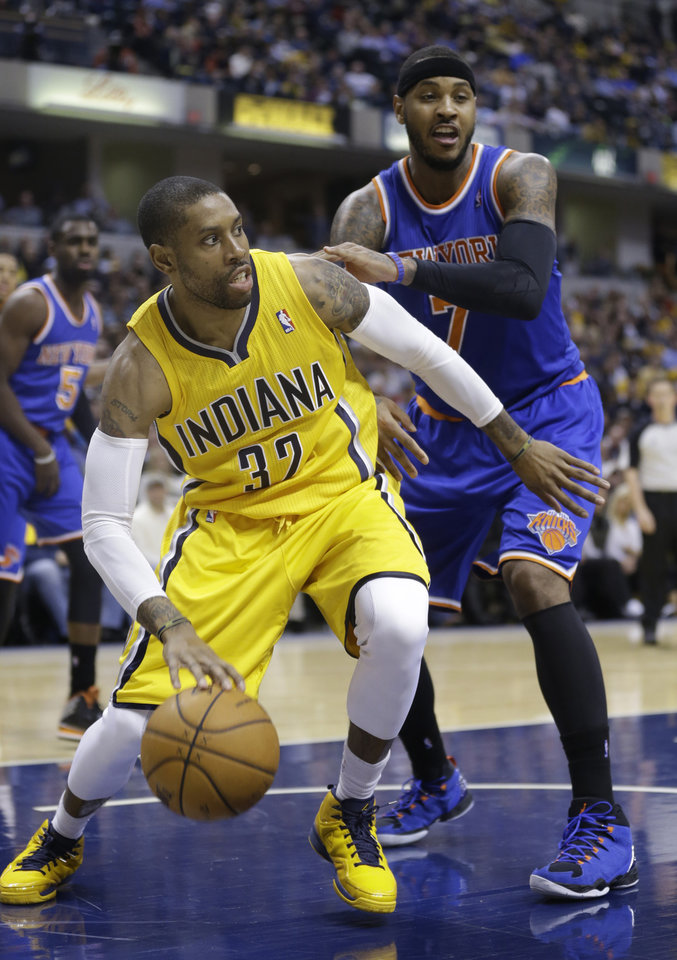 Photo - Indiana Pacers center Ian Mahinmi, left, cuts in front of New York Knicks forward Carmelo Anthony during the second half of an NBA basketball game in Indianapolis, Thursday, Jan. 16, 2014. The Pacers defeated the Knicks 117-89. (AP Photo/Michael Conroy)