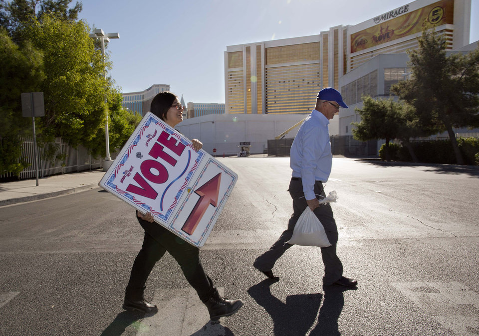 Photo -   In this Oct. 20, 2012, photo, election workers Elena Soto, left, and Dave Carlson post early voting signs for a polling place along Frank Sinatra Blvd. behind The Mirage Hotel-Casino in Las Vegas. The nation's complexion is rapidly changing. A more racially and ethnically diverse population is rising so that, perhaps within three decades, whites will no longer be the majority. That means shifts in political power, the risk of intensified racial tensions and also the opportunity to forge a multiracial society unlike anything in America's past. (AP Photo/Julie Jacobson)