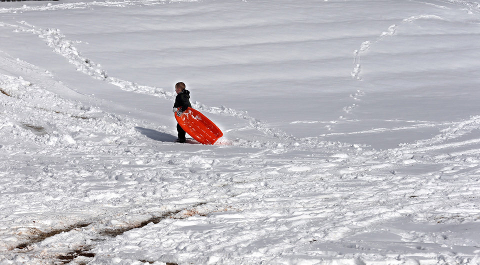 Photo - Jett Campbell walks up  a hill while sledding in a neighborhood near 164th and Penn in northwest Oklahoma City, Okla.,  Friday, Dec. 6, 2013. Photo by Sarah Phipps, The Oklahoman