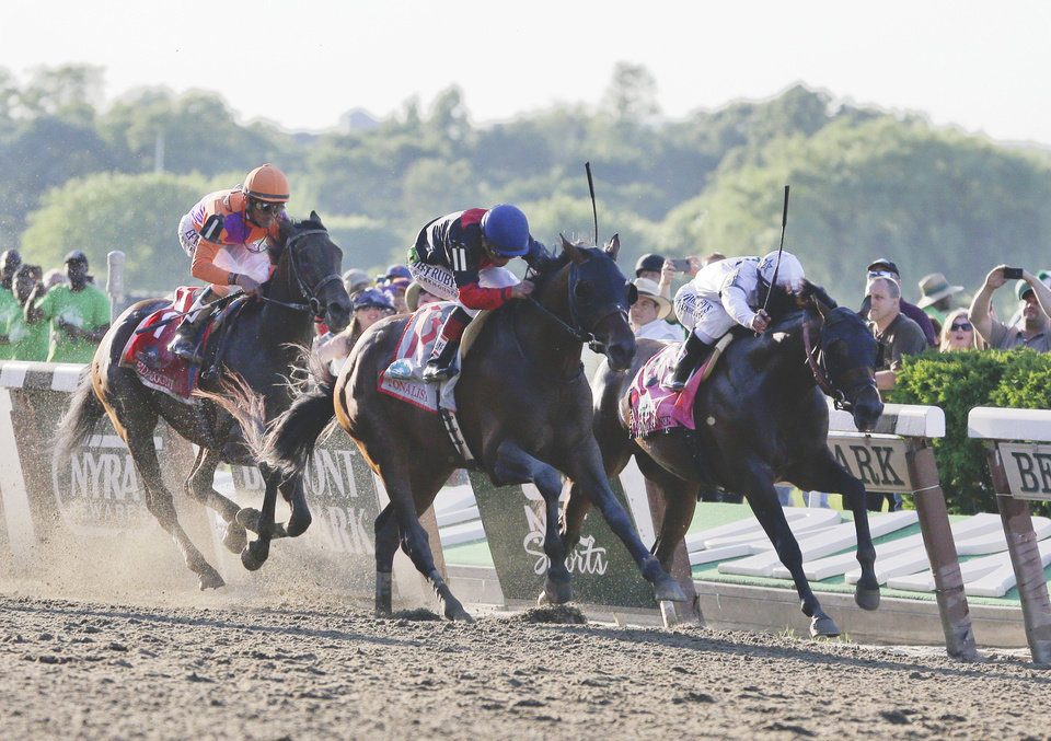 Photo - Tonalist, center, with Joel Rosario, up beats Commissioner, right, with Javier Castellano up, to win the Belmont Stakes horse race, Saturday, June 7, 2014, in Elmont, N.Y. Medal Count, at left, with Robby Albarado up, finished third. (AP Photo/Seth Wenig)