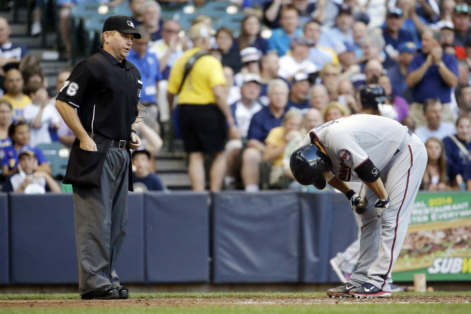 Photo - Home plate umpire Mike Muchlinski watches as Minnesota Twins' Kurt Suzuki, right, reacts after striking out during the fourth inning of a baseball game against the Milwaukee Brewers, Monday, June 2, 2014, in Milwaukee. (AP Photo/Morry Gash)