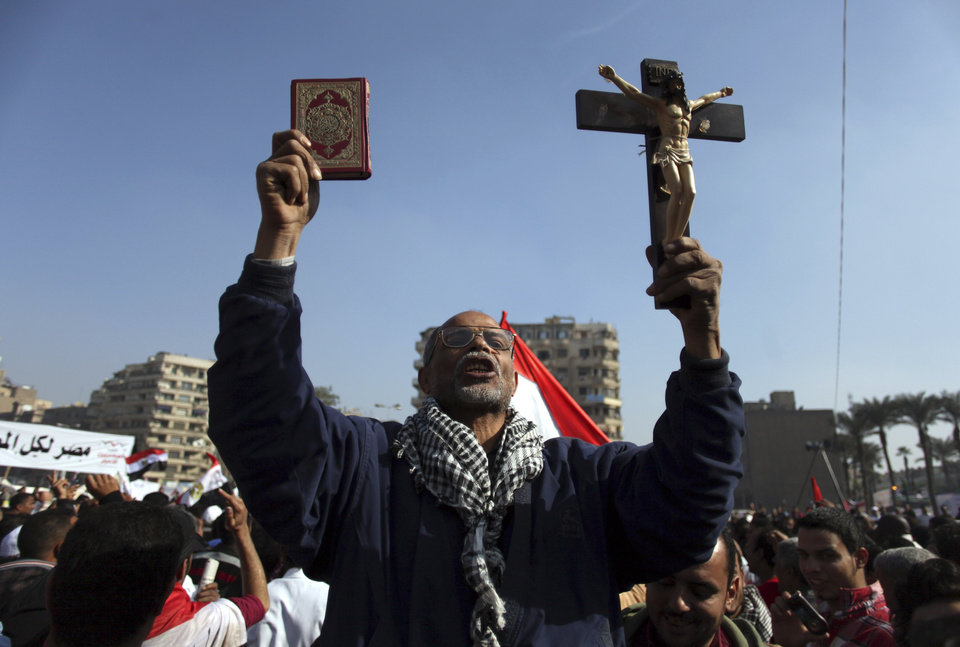 "An Egyptian protesters holds a cross and a Quran as he chants anti-Muslim Brotherhood slogans at an opposition rally in Tahrir Square, in Cairo, Egypt, Friday, Nov. 30, 2012. Egypt's opposition has called for a major rally Friday in Cairo's Tahrir Square, where some demonstrators have camped out in tents since last week to protest decrees that President Mohammed Morsi issued to grant himself sweeping powers. Hundreds gathered in the plaza for traditional Friday prayers, then broke into chants of ""The people want to bring down the regime!"" — echoing the refrain of the Arab Spring revolts, but this time against a democratically elected leader. Other cities around Egypt braced for similar protests. (AP Photo/Khalil Hamra)"