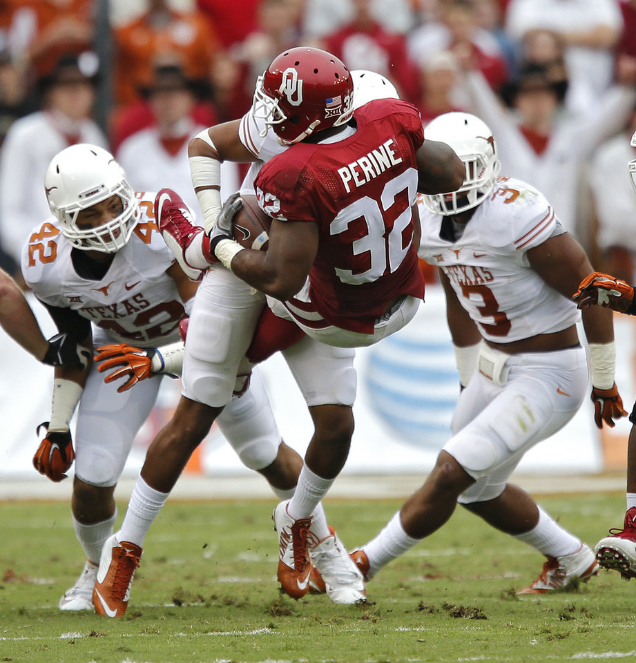 Photo - Oklahoma's Samaje Perine (32) is picked up off the ground as he is brought down by the Texas defense during the college football game between the University of Oklahoma Sooners (OU) and the University of Texas Longhorns (UT) during the Red River Showdown at the Cotton bowl in Dallas, Texas on Saturday, Oct. 11, 2014. Photo by Chris Landsberger, The Oklahoman