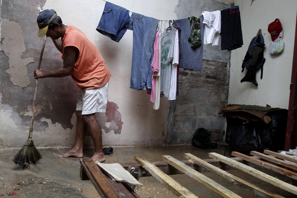 Photo -   Jose Aguilera seeps his home's floor by his empty bed frame after the passing hurricane Sandy damaged his roof, causing rain to soak his mattress, in Gibara, Cuba, Thursday, Oct. 25, 2012. Hurricane Sandy blasted across eastern Cuba on Thursday as a potent Category 2 storm and headed for the Bahamas after causing at least two deaths in the Caribbean. (AP Photo/Franklin Reyes)