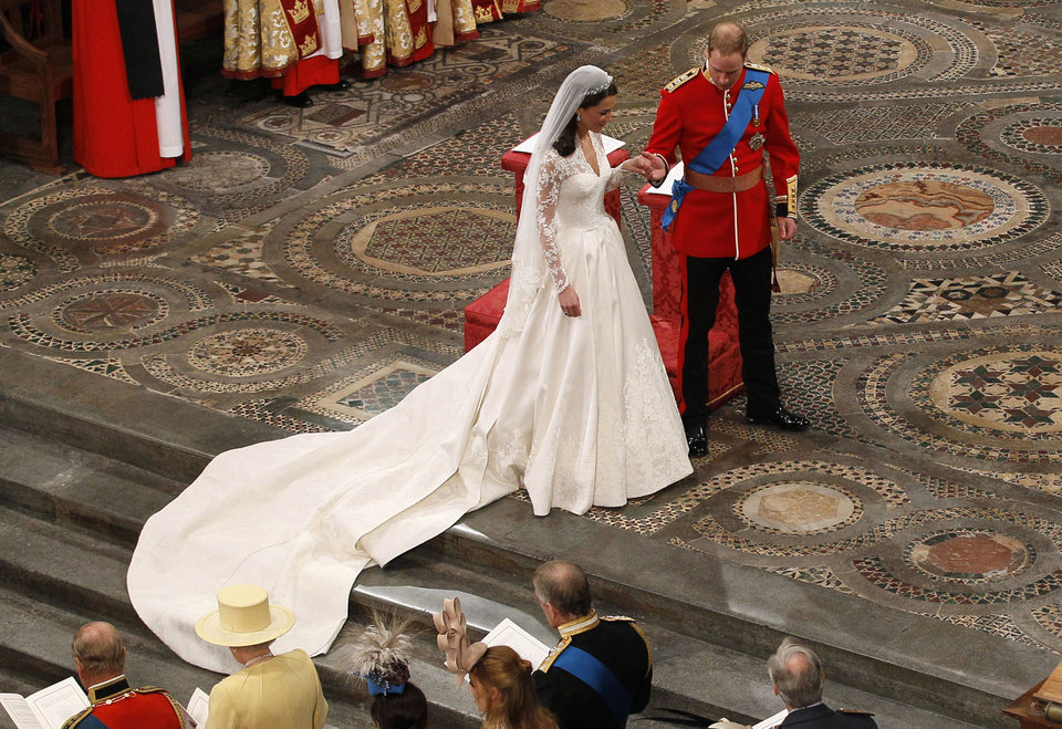 Photo - Britain's Prince William, center right, and his wife Kate, the Duchess of Cambridge, center left, hold hands during their wedding service at Westminster Abbey in London, Friday, April 29, 2011. (AP Photo/Kirsty Wigglesworth, Pool)