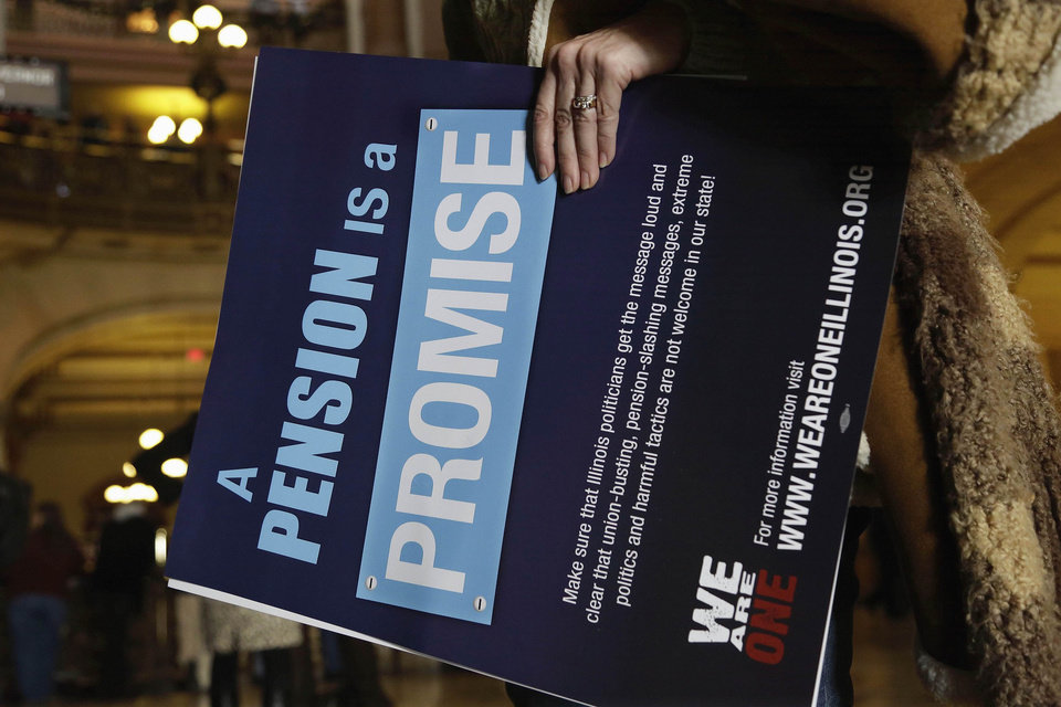 Photo - ADVANCE FOR USE SUNDAY, DEC. 22 AND THEREAFTER - FILE - In this Jan. 3, 2013 file photo, a sign is carried during a rally by Illinois state union members and supporters in support for fair pension reform at the Illinois State Capitol in Springfield. In december Gov. Pat Quinn signed the pension overhaul legislation bill in Chicago. The passing of the landmark $160 billion legislation was voted the top story in Illinois for 2013. (AP Photo/Seth Perlman, File)