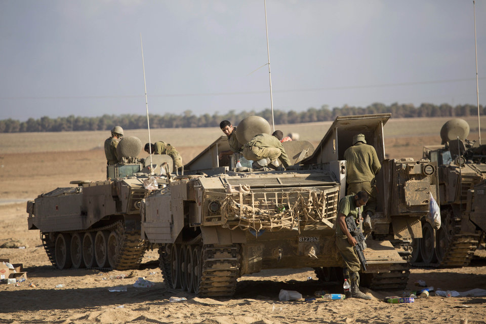 Photo - Israeli soldiers work on their armored personnel carriers near the Israel and Gaza border Friday, July 25, 2014. Early Friday, Israeli warplanes struck tens of houses throughout the Gaza Strip as international efforts continue to broker a cease fire in the 18 day-old war. (AP Photo/Dusan Vranic)