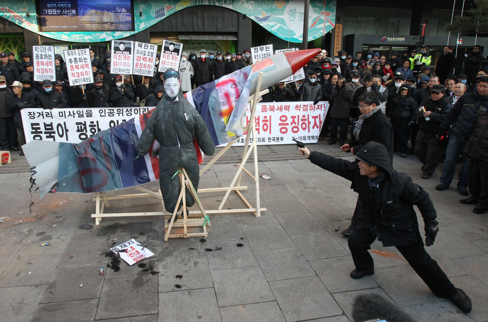 A South Korean protester aims a toy gun at an effigy of North Korean leader Kim Jong Un during a rally denouncing North Korea's rocket launch in Seoul, South Korea, Wednesday, Dec. 12, 2012.  North Korea successfully fired a long-range rocket on Wednesday, defying international warnings as the regime of Kim Jong Un took a giant step forward in its quest to develop the technology to deliver a nuclear warhead.  (AP Photo/Ahn Young-joon) ORG XMIT: SEL107