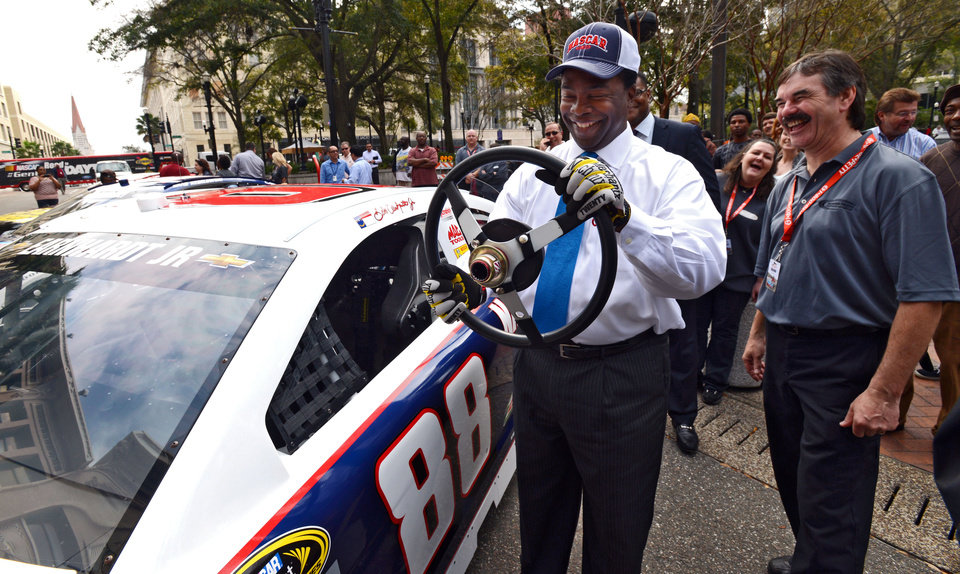 Photo - Jacksonville Mayor Alvin Brown pretends to drive the No. 88 Chevrolet SS of Dale Earnhardt Jr., during NASCAR day Tuesday, Feb. 12, 2013, in Jacksonville, Fla.  The event is part a multi-city media blitz introducing the 2013 NASCAR Sprint Cup Series Chevrolet SS, Ford Fusion and Toyota Camry race cars.  (AP Photo/The Florida Times-Union, Bob Mack) MAGS OUT. TV OUT