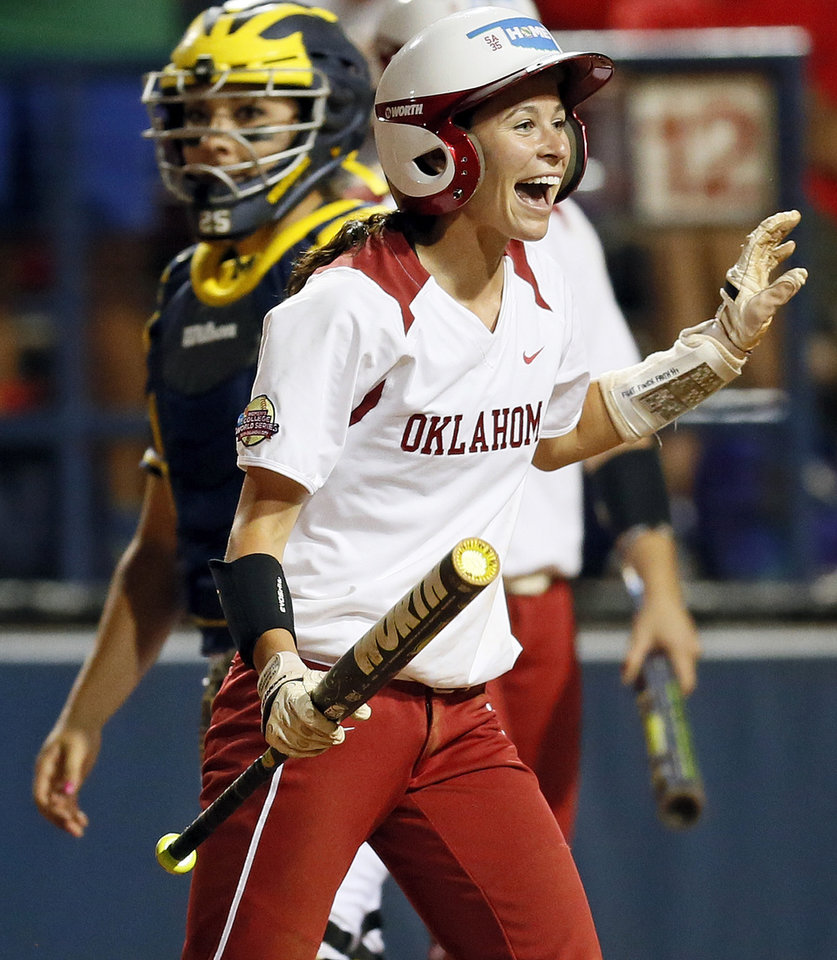 Photo - OU's Brianna Turang (2) reacts in front of Michigan catcher Lauren Sweet (25) after scoring in the third inning during an NCAA softball game in the Women's College World Series between Oklahoma and Michigan at ASA Hall of Fame Stadium, Thursday, May 30, 2013. Photo by Nate Billings, The Oklahoman