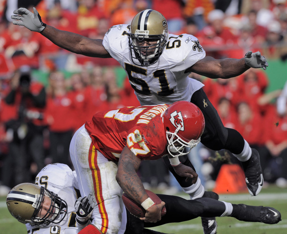 Photo -   FILE - This Nov. 16, 2008 file photo shows New Orleans Saints linebacker Jonathan Vilma (51) flying in to help stop Kansas City Chiefs running back Larry Johnson (27) as he's tied up by New Orleans Saints linebacker Scott Fujita, lower left, late in the second quarter of an NFL football game in Kansas City, Mo. Vilma has been suspended without pay for the entire 2012 season by the NFL, one of four players punished for participating in a pay-for-pain bounty system. NFL Commissioner Roger Goodell's ruling was announced Wednesday, May 2, 2012 . (AP Photo/Reed Hoffmann, File)
