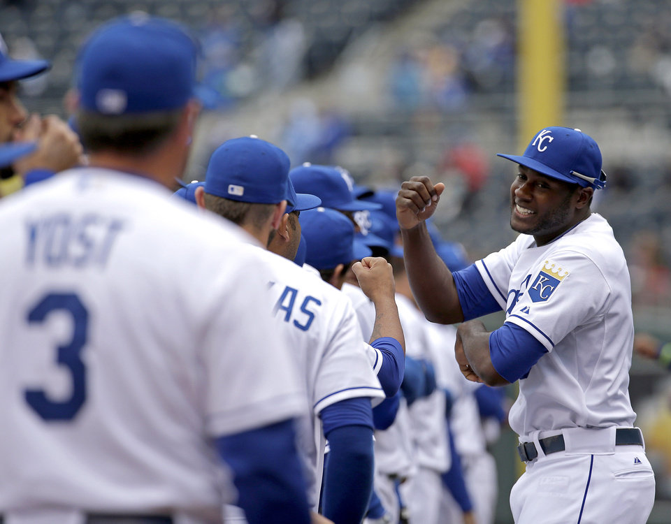 Photo - Kansas City Royals' Lorenzo Cain greets teammates during introductions for a home opener baseball game against the Chicago White Sox, Friday, April 4, 2014, in Kansas City, Mo. (AP Photo/Charlie Riedel)