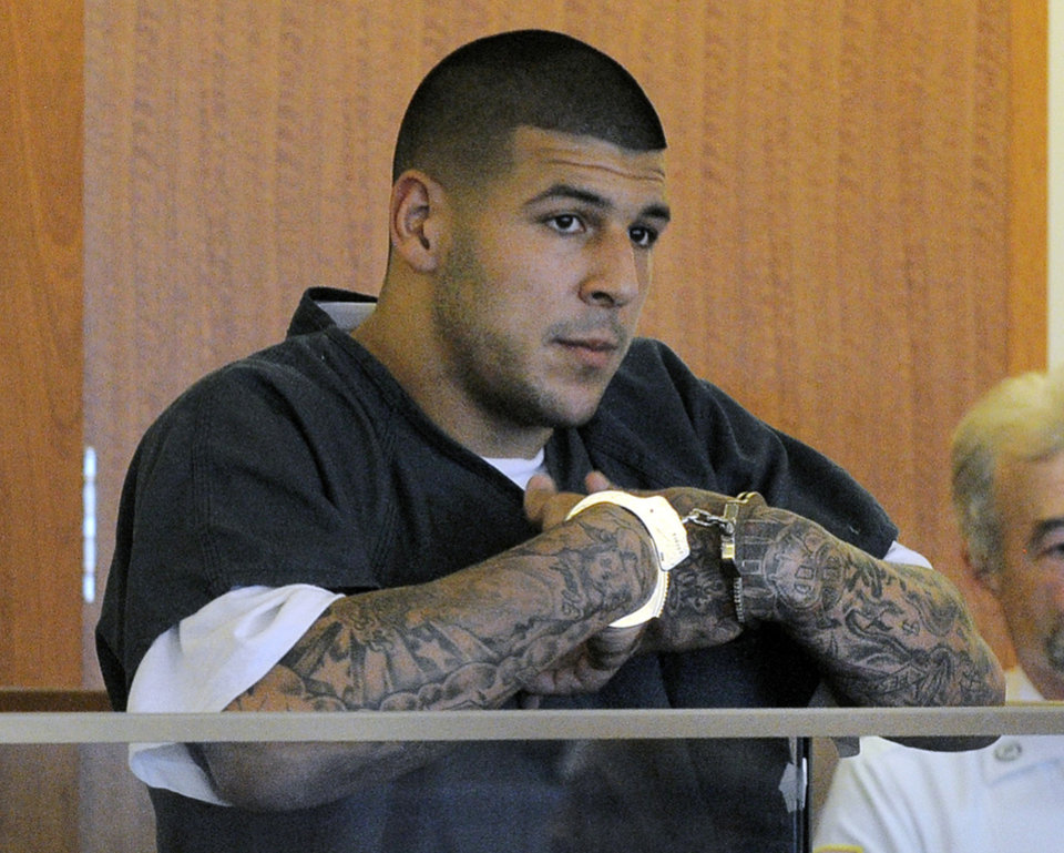 Photo - FILE - Former New England Patriots football tight end Aaron Hernandez stands during a bail hearing in Fall River Superior Court in this June 27, 2013 file photo taken in Fall River, Mass. An associate of former New England Patriots tight end Aaron Hernandez said he was told Hernandez fired the shots that resulted in the death of a semi-pro football player, according to documents filed in Florida.  The records say Hernandez associate Carlos Ortiz told Massachusetts investigators that another man, Ernest Wallace, said Hernandez shot Lloyd in an industrial park near Hernandez's home in North Attleborough. (AP Photo/Boston Herald, Ted Fitzgerald, Pool)