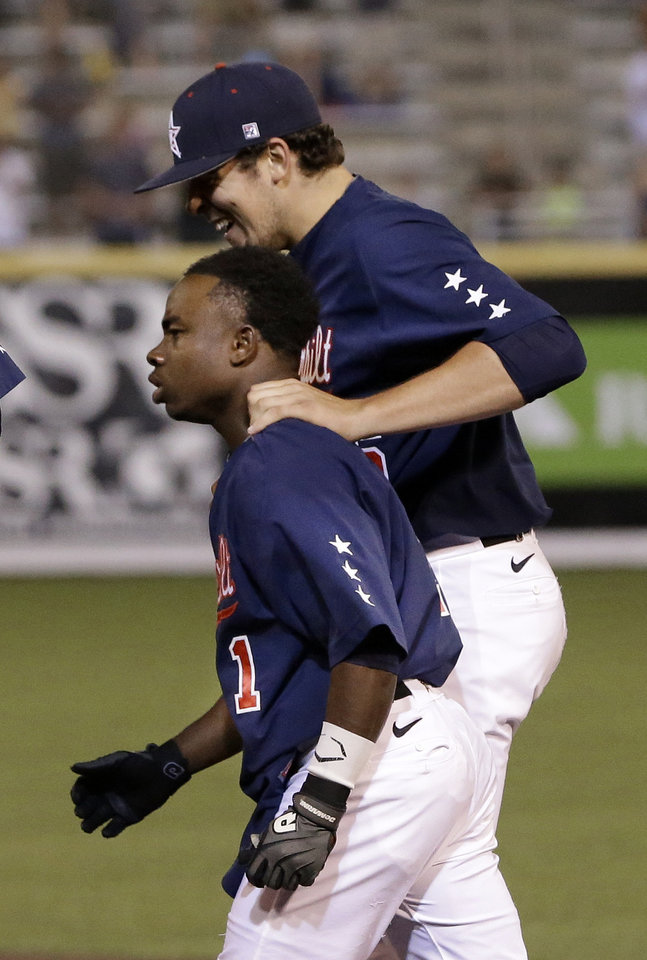 Photo - Vanderbilt pitcher Ben Bowden, right, celebrates with Ro Coleman after Coleman knocked in the winning run with a pinch-hit single in the bottom of the ninth inning to give Vanderbilt a 3-2 win over Oregon of an NCAA college baseball regional tournament game Sunday, June 1, 2014, in Nashville, Tenn. (AP Photo/Mark Humphrey)
