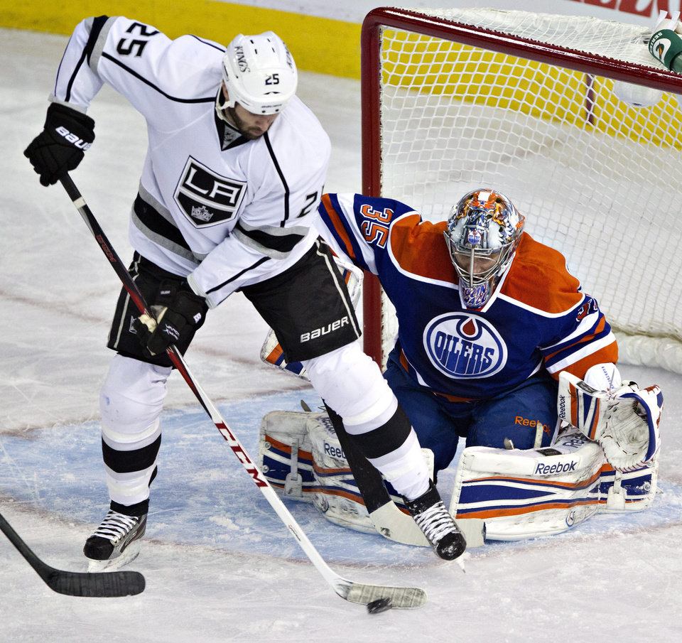 Los Angeles Kings' Dustin Penner (25) deflects the puck as Edmonton Oilers goalie Nikolai Khabibulin (35) makes the save during the first period of their NHL hockey game, Tuesday, Feb. 19, 2013, in Edmonton, Alberta. (AP Photo/The Canadian Press, Jason Franson)