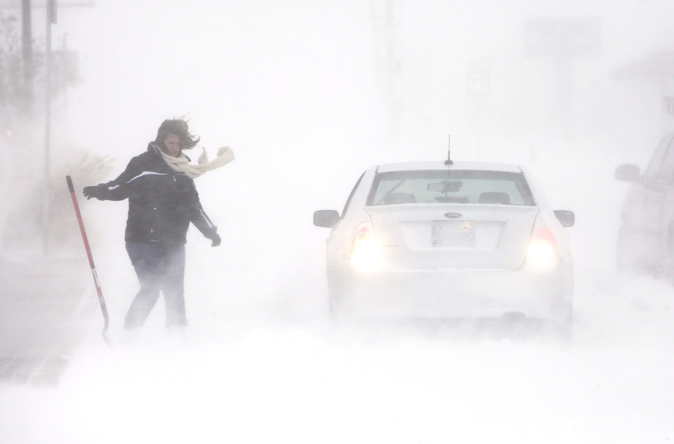 Photo - A stranded motorist reaches for her shovel to try and dig out her car on 15th just west of Broadway in Edmond, Tuesday, February 1, 2011.      Photo by David McDaniel, The Oklahoman