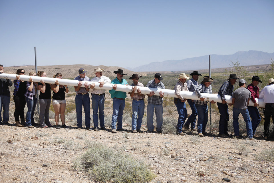 Photo - People help erect a pole to hang a banner during a rally in support of Cliven Bundy near Bunkerville Nev. Monday, April 7, 2014, 2014. The Bureau of Land Management has begun to round up what they call