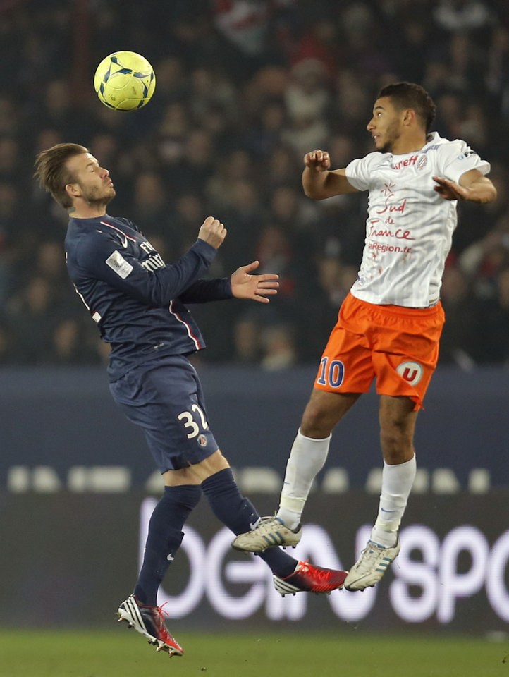 Paris Saint Germain's David Beckham, left vies for the ball with Montpellier's Younes Belhanda during their League One soccer match between PSG and Montpellier at Parc des Princes Stadium, in Paris, Friday March 29, 2013. (AP Photo/Francois Mori)