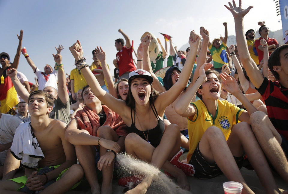 Photo - Soccer fans, many supporting Germany, raise their arms and cheer at the FIFA Fan Fest area on Copacabana beach, after Thomas Mueller scored Germany's fourth goal against Portugal on Monday, June 16, 2014  in Rio de Janeiro, Brazil, during Germany's World Cup soccer match with Portugal.(AP Photo/Wong Maye-E)
