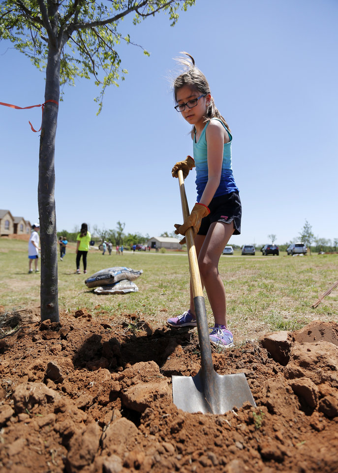 Photo -  Eleanor Harris, 11, shovels dirt as youths and parents from the Inter-Congregational Sunday School of Temple B'nai Israel and Emanuel Synagogue plant trees on a family's Oklahoma City acreage that was damaged during the May 20, 2013 tornado. Photo by Nate Billings, The Oklahoman   NATE BILLINGS -