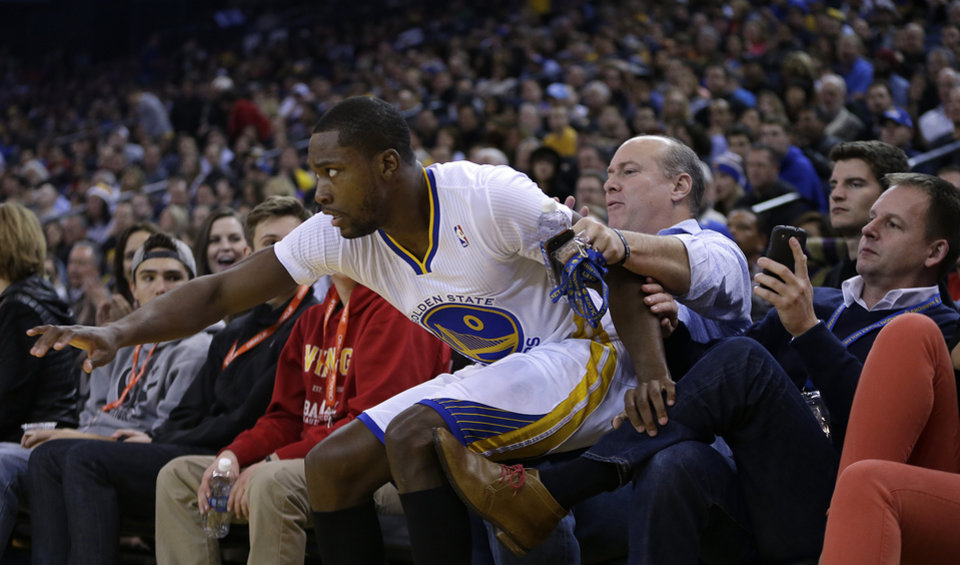 Photo - Golden State Warriors' Toney Douglas lands on fans during the second half of an NBA basketball game against the Los Angeles Lakers, Saturday, Dec. 21, 2013, in Oakland, Calif. (AP Photo/Ben Margot)