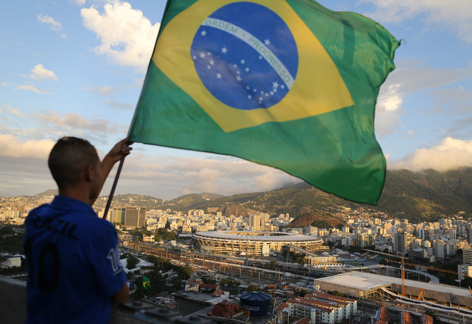 Photo - A youth waves a Brazilian national flag on a rooftop in the Mangueira slum, backdropped by Maracana Stadium, in Rio de Janeiro, Brazil, Thursday, June 12, 2014, as he waits for the broadcast of the World Cup opening match between Brazil and Croatia. Brazil won Croatia 3-1. (AP Photo/Leo Correa)