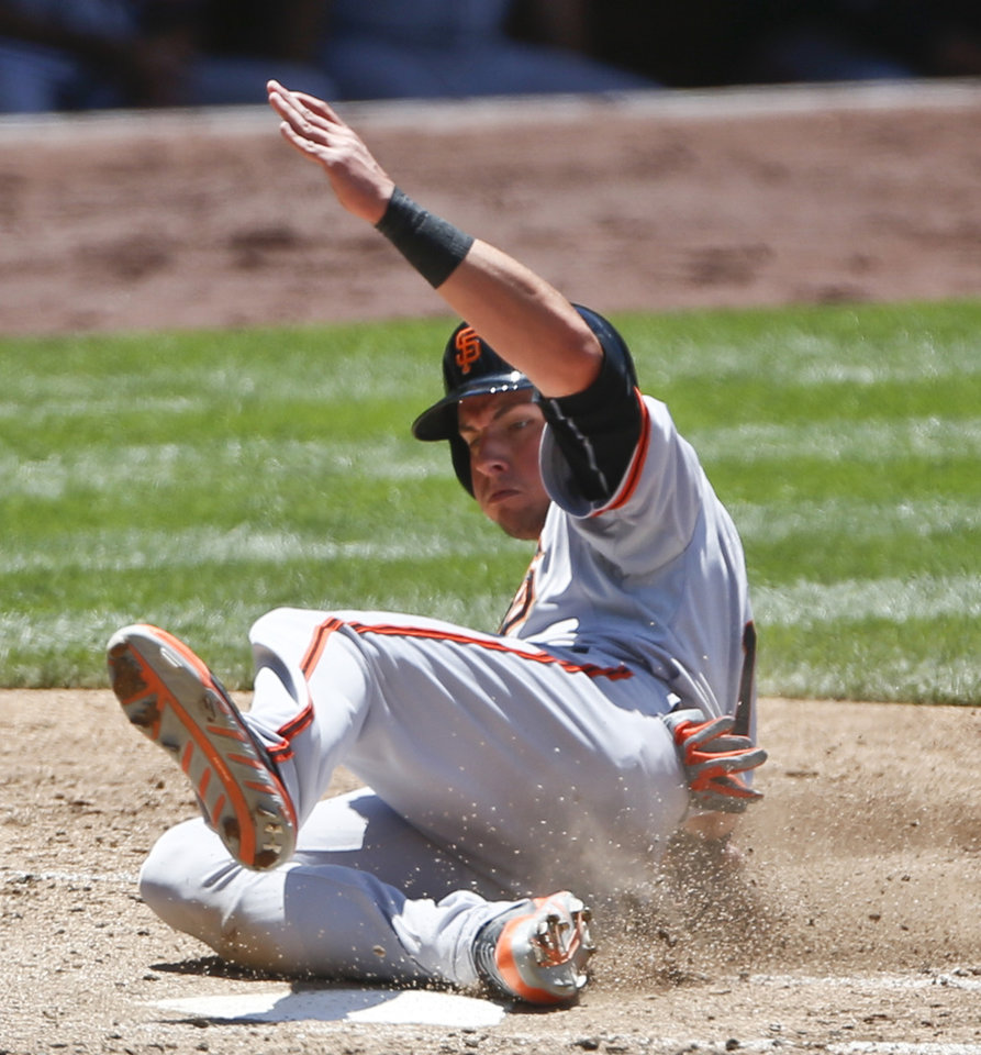 Photo - San Francisco Giants' Joe Panik slides in with th third Giants' run against the San Diego Padres in the third inning of a baseball game Sunday, July 6, 2014, in San Diego.  (AP Photo/Lenny Ignelzi)