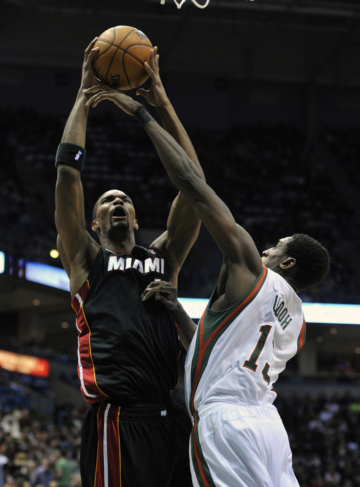 Miami Heat's Chris Bosh left, shoots over Milwaukee Bucks' Ekpe Udoh during the first half of an NBA basketball game on Saturday, Dec. 29, 2012, in Milwaukee. (AP Photo/Jim Prisching)