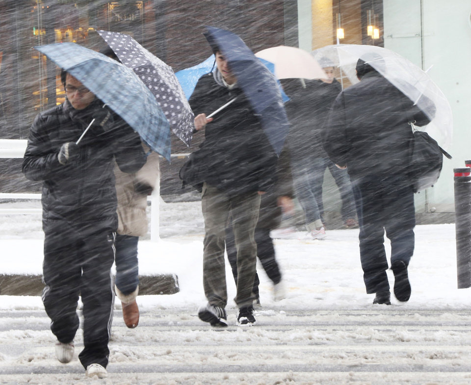 Photo - People walk against blowing snow in Tokyo, Saturday, Feb. 8, 2014. The Japan Meteorological Agency issued Saturday the first heavy snowfall warning for central Tokyo in 13 years.  (AP Photo/Koji Sasahara)