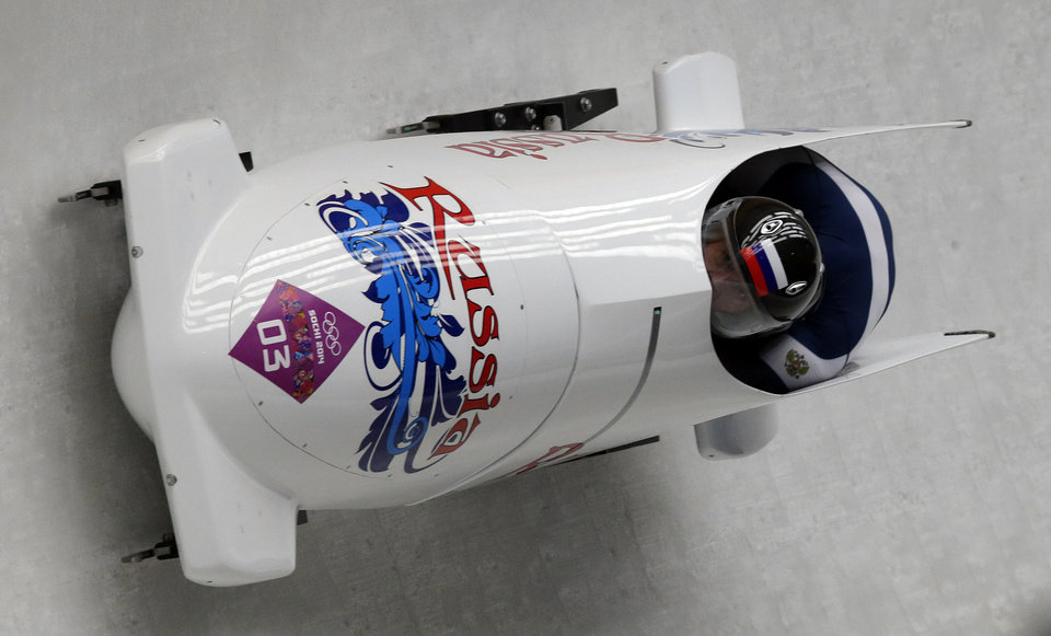 Photo - The team from Russia RUS-1, piloted by Alexander Zubkov and brakeman  Alexey Voevoda, take a curve during the men's two-man bobsled competition at the 2014 Winter Olympics, Sunday, Feb. 16, 2014, in Krasnaya Polyana, Russia. (AP Photo/Michael Sohn)