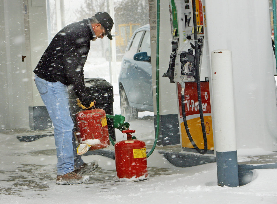 Photo - Tom Hatley fills gas cans for work as the second round of snow in a week moved into the area on Wednesday, February 9, 2011, in Norman, Okla.   Photo by Steve Sisney, The Oklahoman