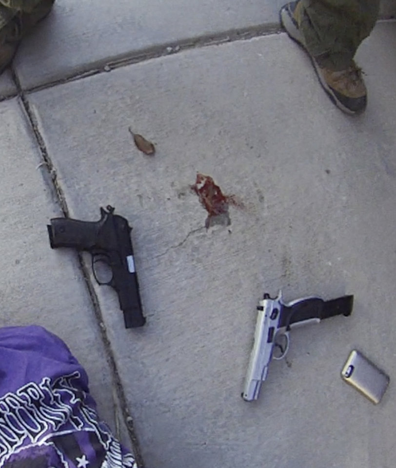 Photo - In this still shot May 3, 2014, taken from an Albuquerque police helmet camera video, a SWAT team unit check Armand Martin, 50, after he was shot by police following a lengthy standoff at an Albuquerque home and find two handguns. Police said the Air Force veteran, whose face is pixelated,  was shot after he came out and fired at officers. He died at the scene. (AP Photo/Courtesy of Albuquerque Police Department)