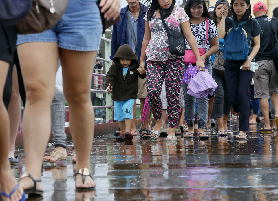 Photo - Pedestrians walk during a slight rain brought about by typhoon Melor (local name