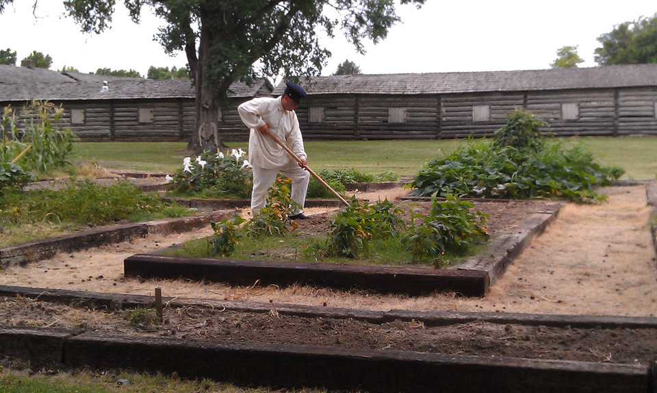 Photo - Correy Twilley, a Fort Gibson historical interpreter, works in the Arbuckle Heritage Garden that soldiers once farmed at the eastern Oklahoma site. PHOTO PROVIDED.