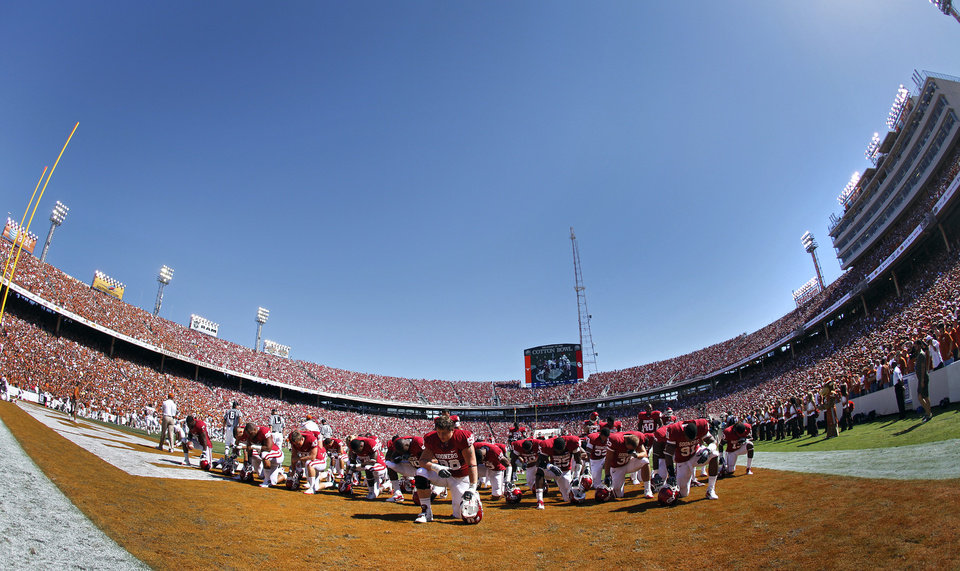 Photo - The Sooners kneel in the end zone before the start of the Red River Rivalry college football game between the University of Oklahoma Sooners (OU) and the University of Texas Longhorns (UT) at the Cotton Bowl on Saturday, Oct. 2, 2010, in Dallas, Texas.   Photo by Chris Landsberger, The Oklahoman