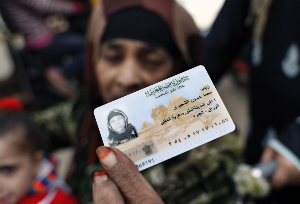 Photo -   Egyptian Zeinab al-Shogery, 58 shows her identification card while she prepares to vote at a polling center in Giza, Egypt Wednesday, Dec. 21, 2011. Voting in election runoffs for Egypt's first parliament since Hosni Mubarak's ouster resumed on Wednesday without the long lines outside polling centers seen in previous rounds of the staggered vote. (AP Photo/Nasser Nasser)