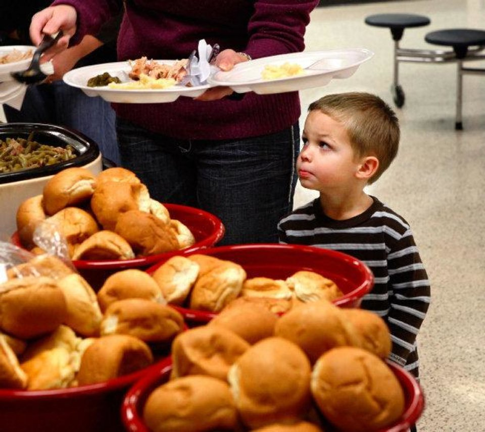 Owen Atteberry, 3, watches his mom, Kristin, put food on his plate as they go through the serving line at Putnam City West High School on Saturday. PHOTO BY JIM BECKEL, THE OKLAHOMAN <strong>JIM BECKEL - THE OKLAHOMAN</strong>