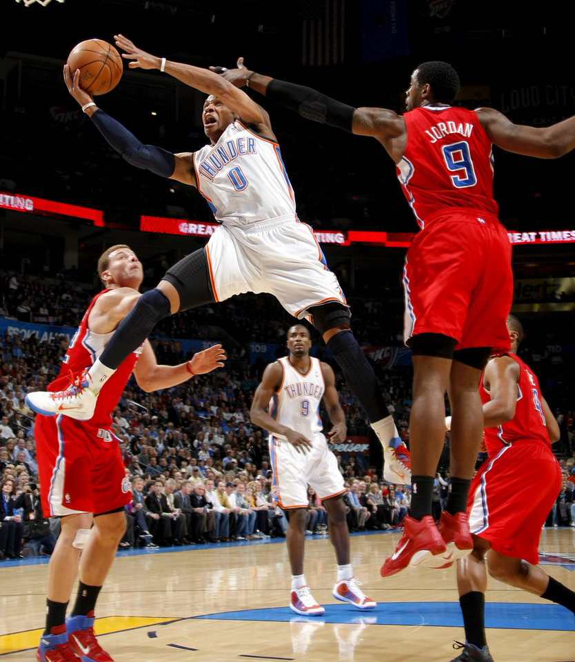 L.A. CLIPPERS: Oklahoma City's Russell Westbrook (0) goes to the basket between Los Angeles' Blake Griffin (32) and DeAndre Jordan (9) during the NBA basketball game between the Oklahoma City Thunder and the Los Angeles Clippers at the Oklahoma CIty Arena, Tuesday, Feb. 22, 2011.  Photo by Bryan Terry, The Oklahoman ORG XMIT: KOD