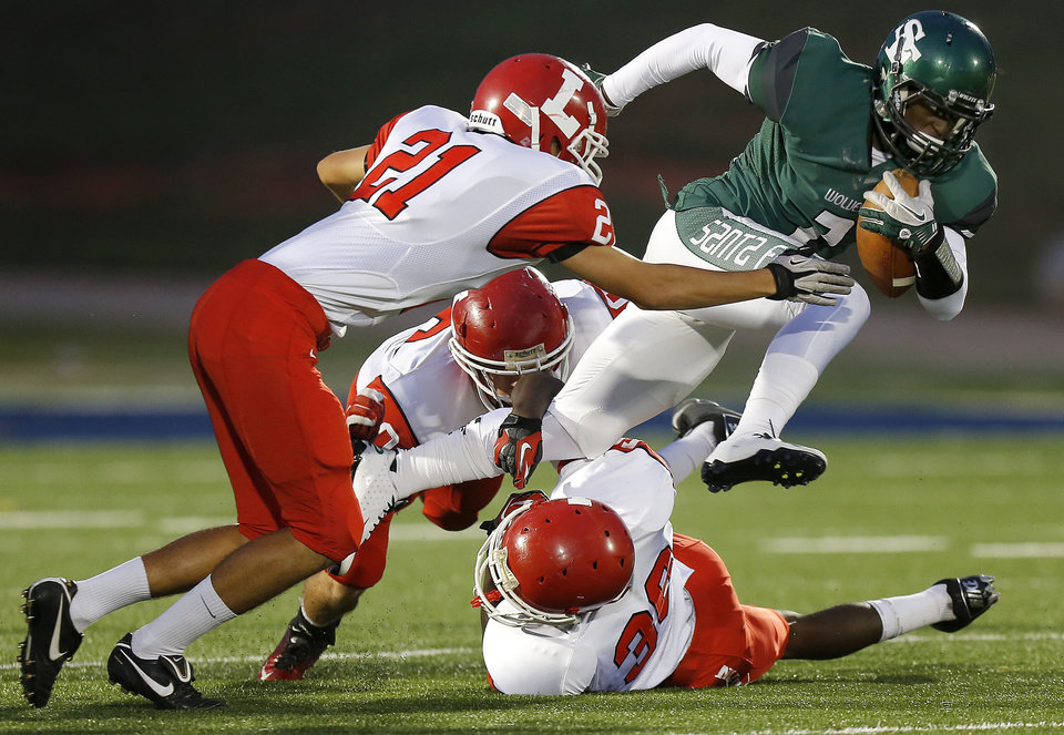 Photo - Edmond Santa Fe's Trevan Smith tries to get past Lawton's Matt Leon, left, Casey Nadeau, and Mike Warren, bottom right, during their high school football game at Wantland Stadium in Edmond, Okla., Thursday, October 11, 2012. Photo by Bryan Terry, The Oklahoman