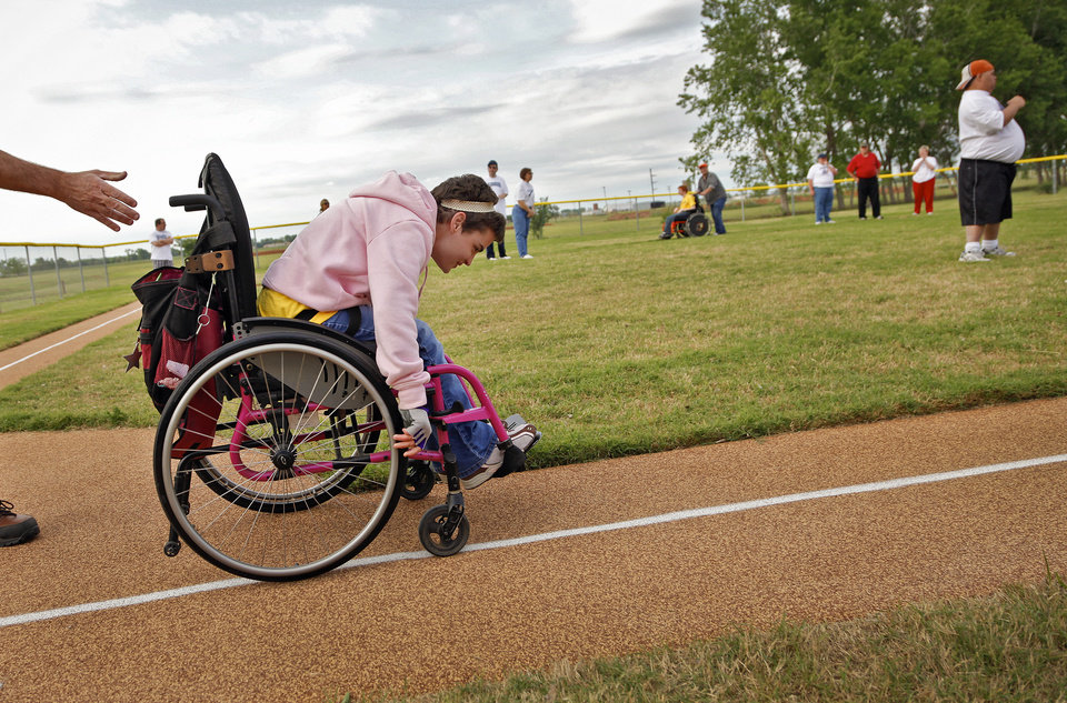 The Coyotes' Caley Carlton gets a push as she makes her way down the first base line during a Yukon Spirit League baseball game at Taylor Park on Tuesday, April 26, 2011, in Yukon, Okla.  Photo by Chris Landsberger, The Oklahoman