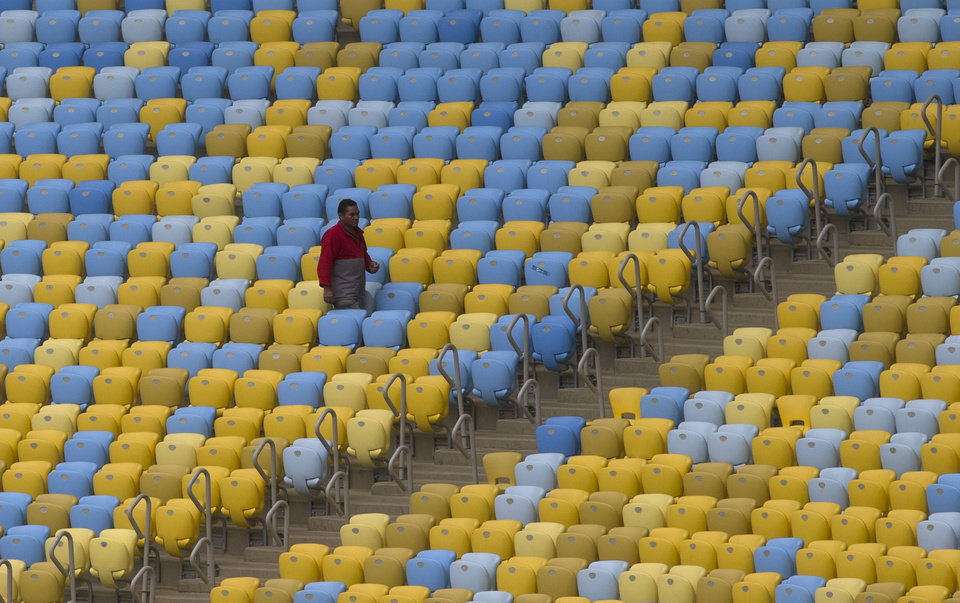 Photo - A worker walks amid the seats of the Maracana stadium during a press tour, in Rio de Janeiro, Brazil, Monday, May 26, 2014. Brazil will host the World Cup soccer tournament starting on 12 June and Maracana stadium will host the World Cup Final match on July 13. (AP Photo/Silvia Izquierdo)