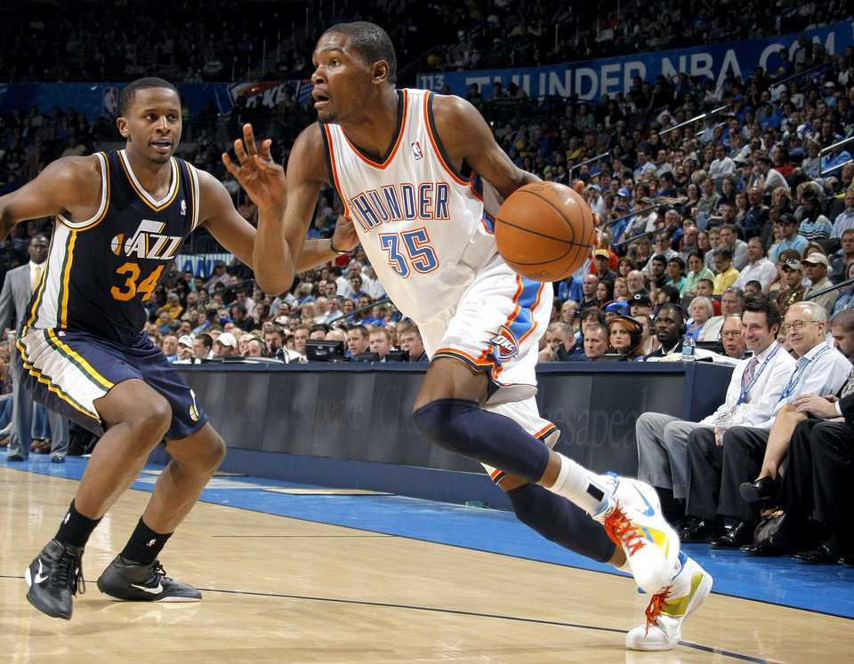 Photo - Oklahoma City's Kevin Durant (35) drives to the basket past Utah's C.J. Miles (34)during the NBA game between the Oklahoma City Thunder and Utah Jazz, Wednesday, March 23, 2011, at the Oklahoma City Arena. Photo by Sarah Phipps, The Oklahoman
