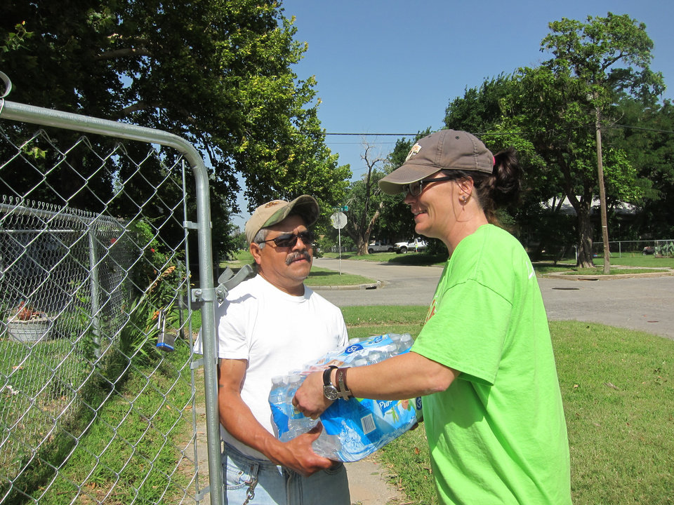 Photo -  Jesus House resident Leslie Stickney, 42, at right, gives a case of bottled water to a resident of the Orchard Park neighborhood during a recent Adopt-A-Block outing. Photo by Carla Hinton, The Oklahoman