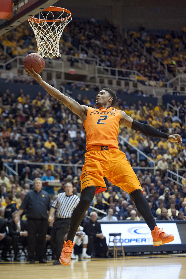 Photo - Oklahoma State's Le'Bryan Nash (2) drives to the basket during the first half of an NCAA college basketball game against West Virginia, Saturday, Jan. 11, 2014, in Morgantown, W.Va. (AP Photo/Andrew Ferguson)