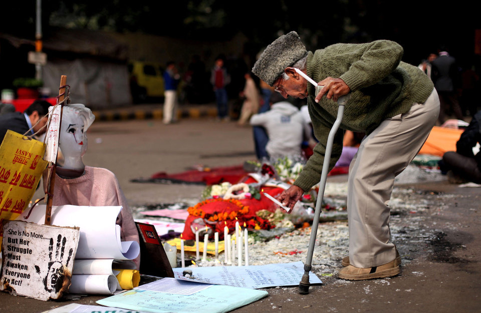 Photo - An elderly Indian man lights a candle at a makeshift memorial of a gang-rape victim in New Delhi, India, Thursday, Jan. 3, 2013. Indian police were preparing Thursday to file rape and murder charges against a group of men accused of sexually assaulting the 23-year-old university student for hours on a moving bus in New Delhi. The Dec. 16 attack on the woman, who later died of her injuries, has caused outrage across India, sparking protests and demands for tough new rape laws, better police protection for women and a sustained campaign to change society's views about women. (AP Photo/Altaf Qadri)